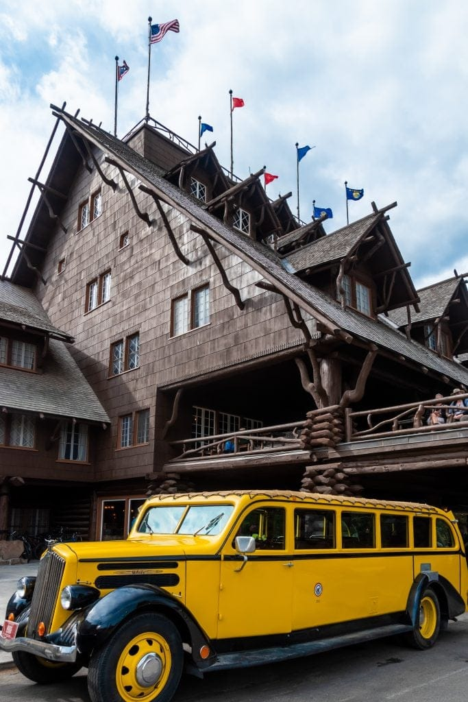A classic yellow tour bus in front of the Old Faithful Inn